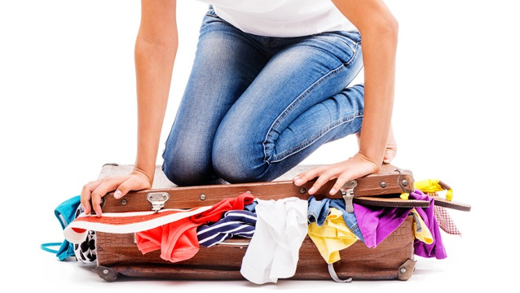 Close-up of girl packing her suitcase