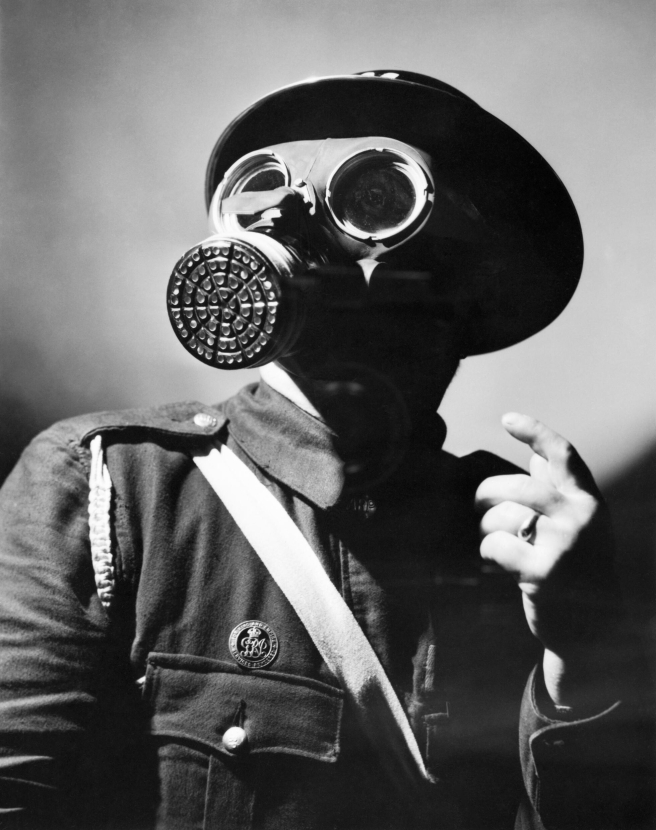 An_Air_Raid_Warden_wearing_his_steel_helmet_and_duty_gas_mask_during_the_Second_World_War._D4054.jpg